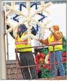FIRST SNOWFLAKES OF THE  SEASON: A Charles City crew puts up Christmas decorations  Thursday on N. Main Street.